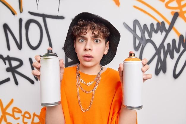 Oszołomiony przystojny hipster facet trzyma dwie butelki z aerozolem, dzięki czemu ściana graffiti nosi kapelusz, a pomarańczowa koszulka niszczy budynki uliczne