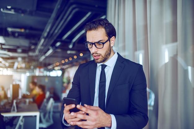 Oszołomiony przystojny kaukaski brodaty biznesmen w garniturze i okularach stoi w towarzystwie i czyta nieprzyjemną wiadomość. ja