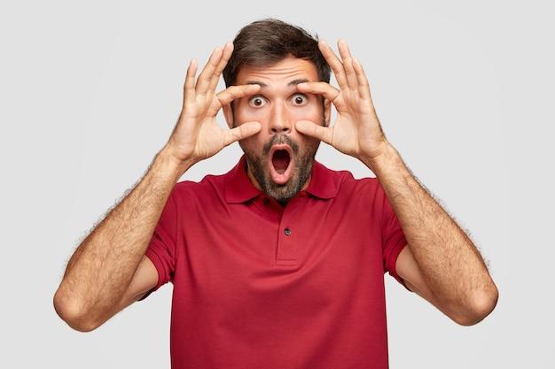 Oszołomiony, wzruszający, brodaty europejczyk z wyskoczonymi oczami, opuszcza szczękę, trzyma ręce na twarzy