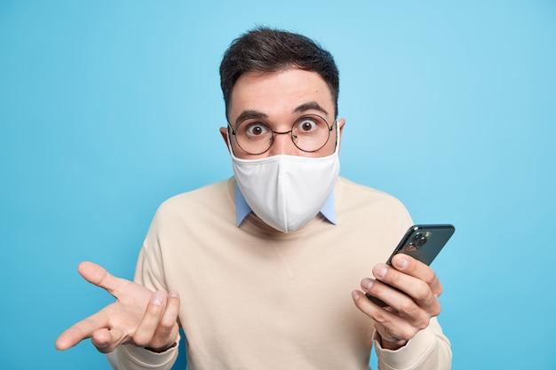 Oszołomiony, zakłopotany dorosły mężczyzna patrzy zszokowany, nosi maskę, aby zapobiec zarażeniu koronawirusem, pozostaje bezpieczny podczas kwarantanny domowej korzysta z telefonu komórkowego