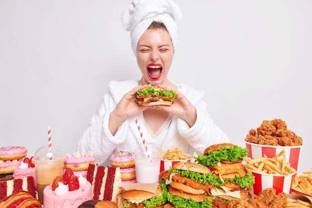 Oszukać mea i obżarstwo. śmieszna młoda kobieta wykrzykuje głośno, trzyma usta szeroko otwarte i je smacznego burgera w otoczeniu różnych fast foodów
