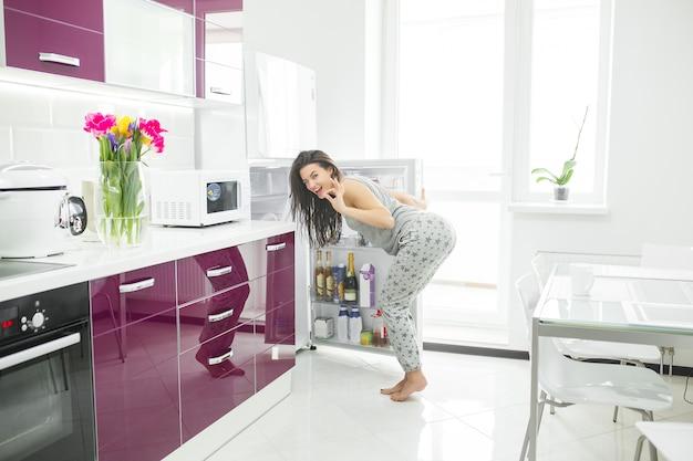 Oszust diety. kobieta w kuchni w pobliżu lodówki. kobieta chce jeść. głodna pani rano.