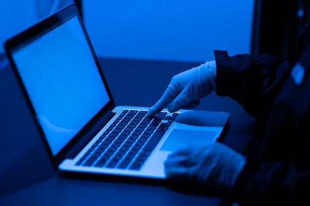 Oszust za pomocą laptopa w celu włamania się lub kradzieży danych w nocy w biurze.