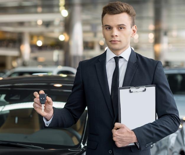 Oto twój klucz! pewny siebie młody sprzedawca klasycznych samochodów stojący w salonie i trzymający kluczyk