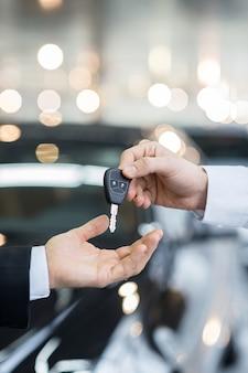 Oto twój klucz! zbliżenie na mężczyznę dającego klucz właścicielowi samochodu stojącego przed samochodem