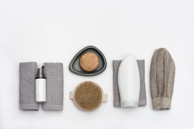 Otoczenie spa do pielęgnacji ciała i zabiegów upiększających. mydło, bawełniany ręcznik, myjka do kąpieli, drewniana szczotka do włosów.