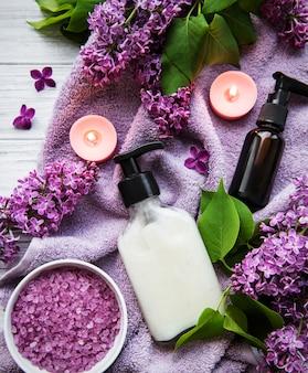Otoczenie spa z kwiatami bzu. sól morska w misce, butelki z olejkiem aromatycznym i świece na drewnianej powierzchni.