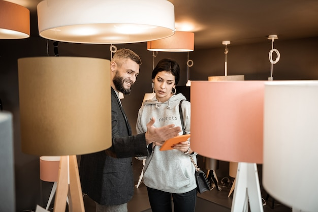 Otoczony lampami. ciekawa para prowadząca ciekawą rozmowę na temat wyglądu swojego domu podczas pobytu w salonie