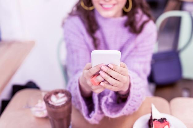 Otoczony smakołykami. uśmiechnięta pozytywna pani niosąca swój biały telefon komórkowy i przyjemnie rozmawiająca