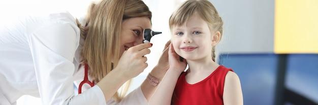 Otolaryngolog bada ucho małej dziewczynki z wadą słuchu u dzieci i ich