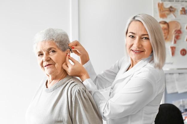 Otolaryngolog zakładający w szpitalu aparat słuchowy do ucha starszej kobiety
