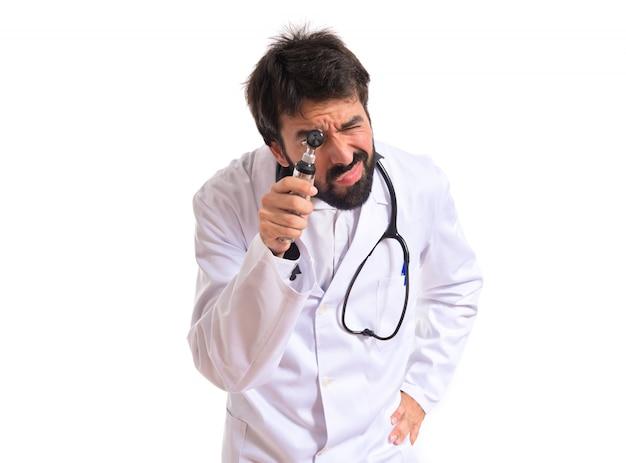Otorhinolaryngologist z jego otoscope na białym tle