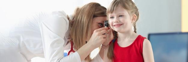 Otorynolaryngolog bada ucho małej dziewczynki. infekcje ucha w koncepcji dzieci