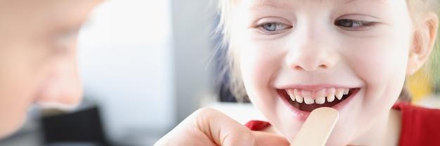 Otorynolaryngolog badający gardło małego dziecka z rozpoznaniem i leczeniem szpatułką