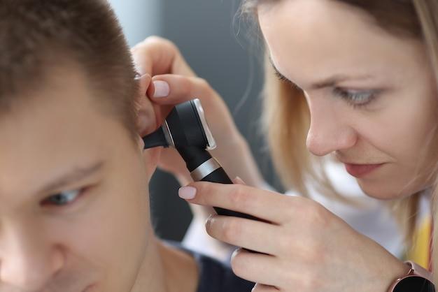 Otorynolaryngolog kobieta patrząc na ucho pacjentów z otoskopem zbliżenie