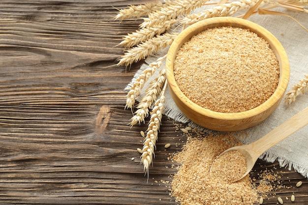 Otręby w misce i pszenne kłosy na brązowym drewnianym stole