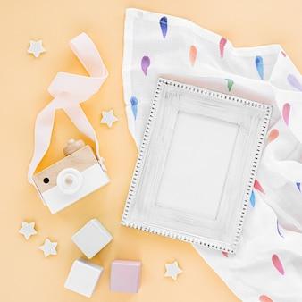 Otulacz muślinowy z ramką na zdjęcie i zabawkami na żółtym tle. zestaw akcesoriów dla noworodków neutralnych pod względem płci. płaski układanie, widok z góry