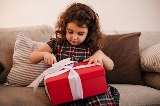 Otwarcie prezent urodzinowy dla brunetki. kryty strzał preteen dziewczyna z prezentem.
