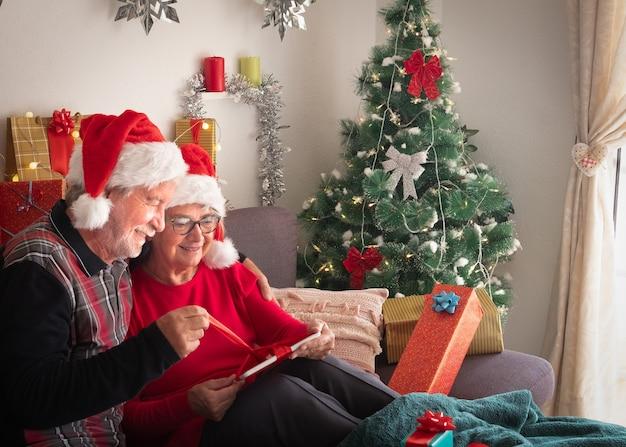 Otwarcie prezentu na boże narodzenie. starsze małżeństwo uśmiecha się radośnie, zdejmując taśmę z otrzymanego nowego tabletu. choinka na tle. biała ściana