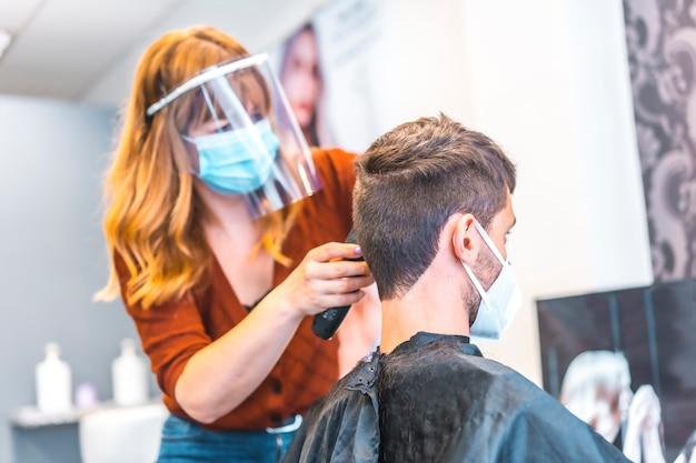 Otwarcie salonów fryzjerskich po pandemii koronawirusa, covid-19. środki bezpieczeństwa, maska na twarz, ekran ochronny, dystans społeczny. fryzjer pracuje nad nową normą