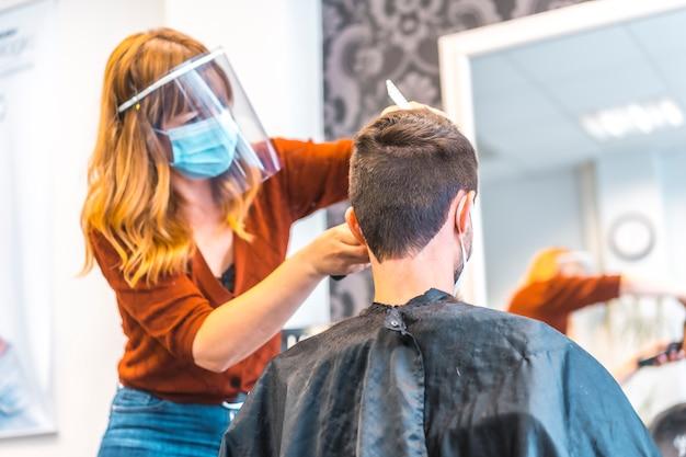 Otwarcie salonów fryzjerskich po pandemii koronawirusa, covid-19. środki bezpieczeństwa, maska na twarz, ekran ochronny, dystans społeczny. fryzjerzy w nowej normalności