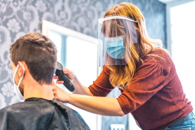 Otwarcie salonów fryzjerskich po pandemii koronawirusa, covid-19. środki bezpieczeństwa, maska na twarz, ekran ochronny, dystans społeczny. kaukaski fryzjer pracuje z plastikowym ekranem