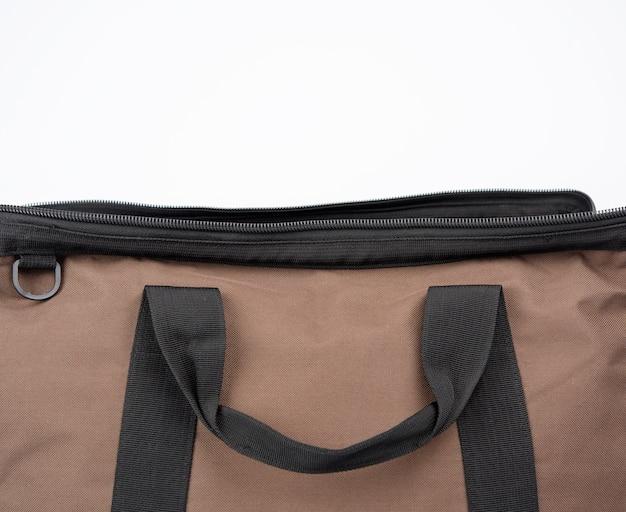 Otwarta brązowa tekstylna torba podróżna z uchwytami na białym tle