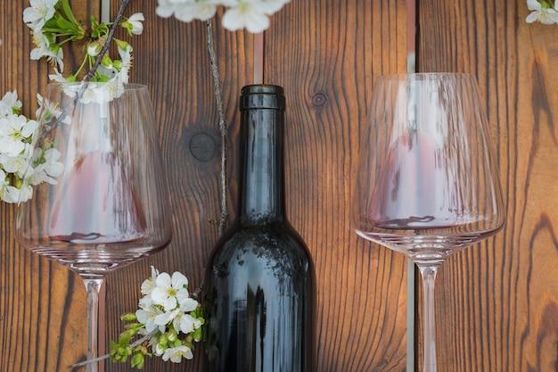 Otwarta butelka wina i dwie szklanki na drewnianym stole z kwiatami wiśni. klasyczne wino i kwiaty wiśni.