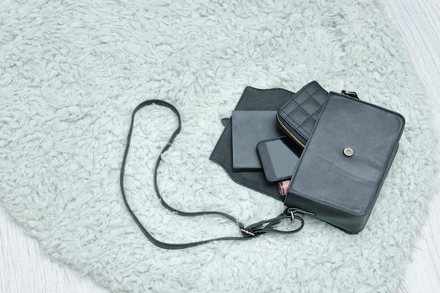 Otwarta czarna torba z upuszczonymi przedmiotami, notatnikiem, telefonem komórkowym i torebką,