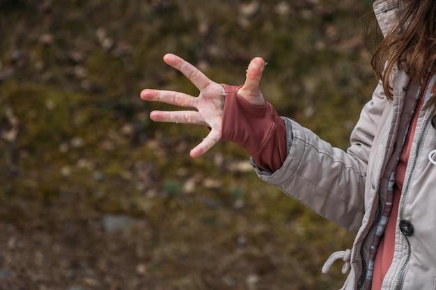 Otwarta dłoń z drobinkami śniegu mokry i zmarznięty kobieca ręka w swetrze z dziurką na kciuk podczas wiosennej wędrówki