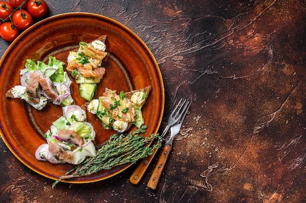 Otwarta kanapka tostowa z łososiem i śledziem, twarożkiem i surówką