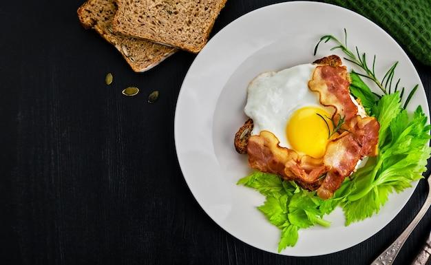 Otwarta kanapka z boczkiem, jajkiem sadzonym i liśćmi selera na kromce chleba żytniego na zakwasie z pestkami dyni na białym talerzu