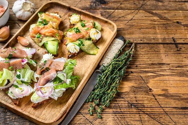 Otwarta kanapka z łososiem i śledziem, twarożkiem i surówką na desce do krojenia. drewniane tła. widok z góry. skopiuj miejsce.