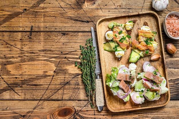 Otwarta kanapka z łososiem i śledziem, twarożkiem i surówką na desce do krojenia