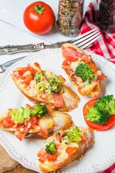 Otwarta kanapka z prosciutto, mozzarella i pomidorów na stole w kuchni, płytkie fokus