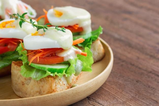 Otwarta kanapka z tostami i warzywnym i gotowanym jajkiem z dressingiem sałatkowym.