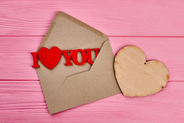 Otwarta koperta i drewniane serce. koperta z papieru kraftowego i czerwony drewniany napis i love you. koncepcja listu miłosnego.