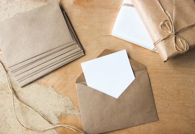 Otwarta koperta z białym papierem firmowym na miejsce na kopię leży na drewnianym przygotowaniu tła