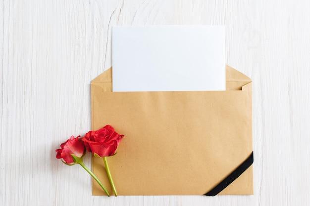Otwarta koperta z czystym papierem i czarną wstążką z dwiema różami