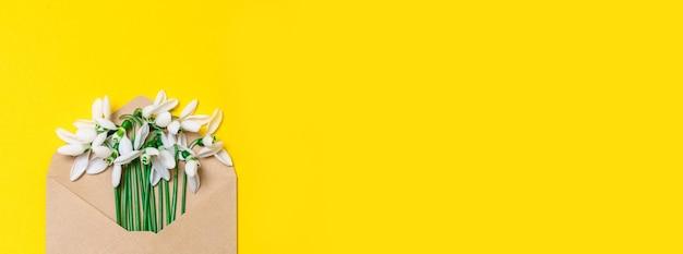 Otwarta koperta z papieru kraftowego z wiosennymi kwiatami na żółtym tle. widok z góry na płasko.