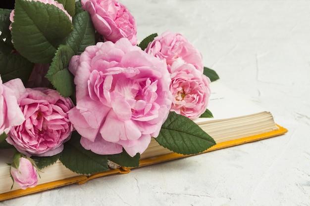 Otwarta książka i róże na lekkiej kamiennej powierzchni.