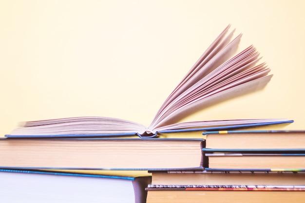 Otwarta książka jest na stosie innych książek w pastelowym kolorze żółtym.
