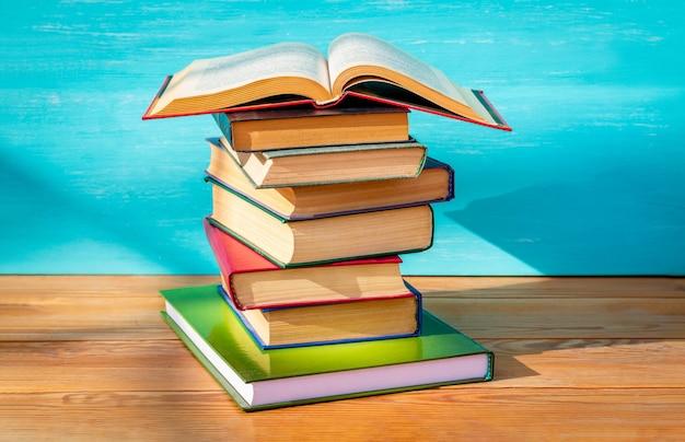Otwarta książka leżąca na stosie książek w słońcu na drewnianym stole.