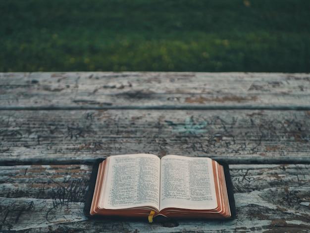 Otwarta książka leży na starej drewnianej ławce