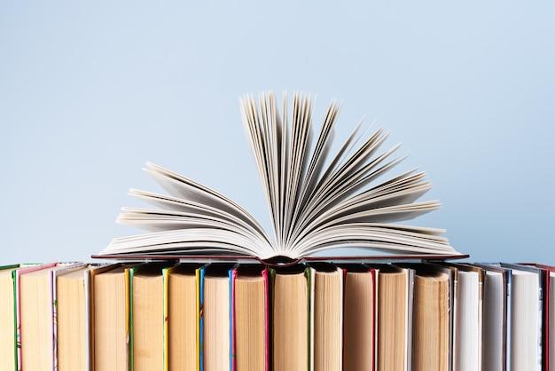 Otwarta książka leży w rzędzie książek w różnych oprawach na jasnoniebieskiej ścianie