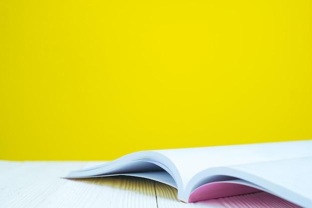 Otwarta książka na bielu stole z żółtym tłem.