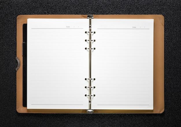 Otwarta książka na ciemnym tle. pusta strona z liniami papieru.