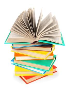 Otwarta książka na stosie wielokolorowych książek. na białym tle.