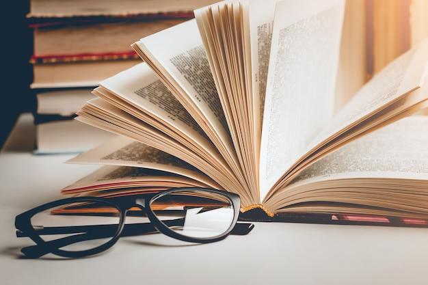 Otwarta książka w okularach na drewnianym stole na tle zestawu książek, vintage tonowanie.