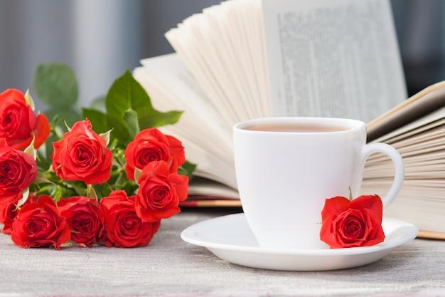 Otwarta książka z czerwonymi pomarańczowymi różami i filiżanką herbaty. czytanie i relaks. romantyczna, słodka, randkowa koncepcja.